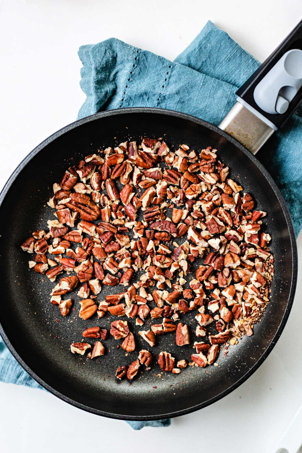 toasted pecans in a non stick skillet on a counter.