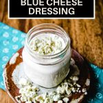 buttermilk blue cheese dressing in a mason jar with blue cheese crumbles on top sitting on a wooden table.