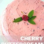 fresh cherry cake with a cherry and mint leaves on top on a cake pedestal.
