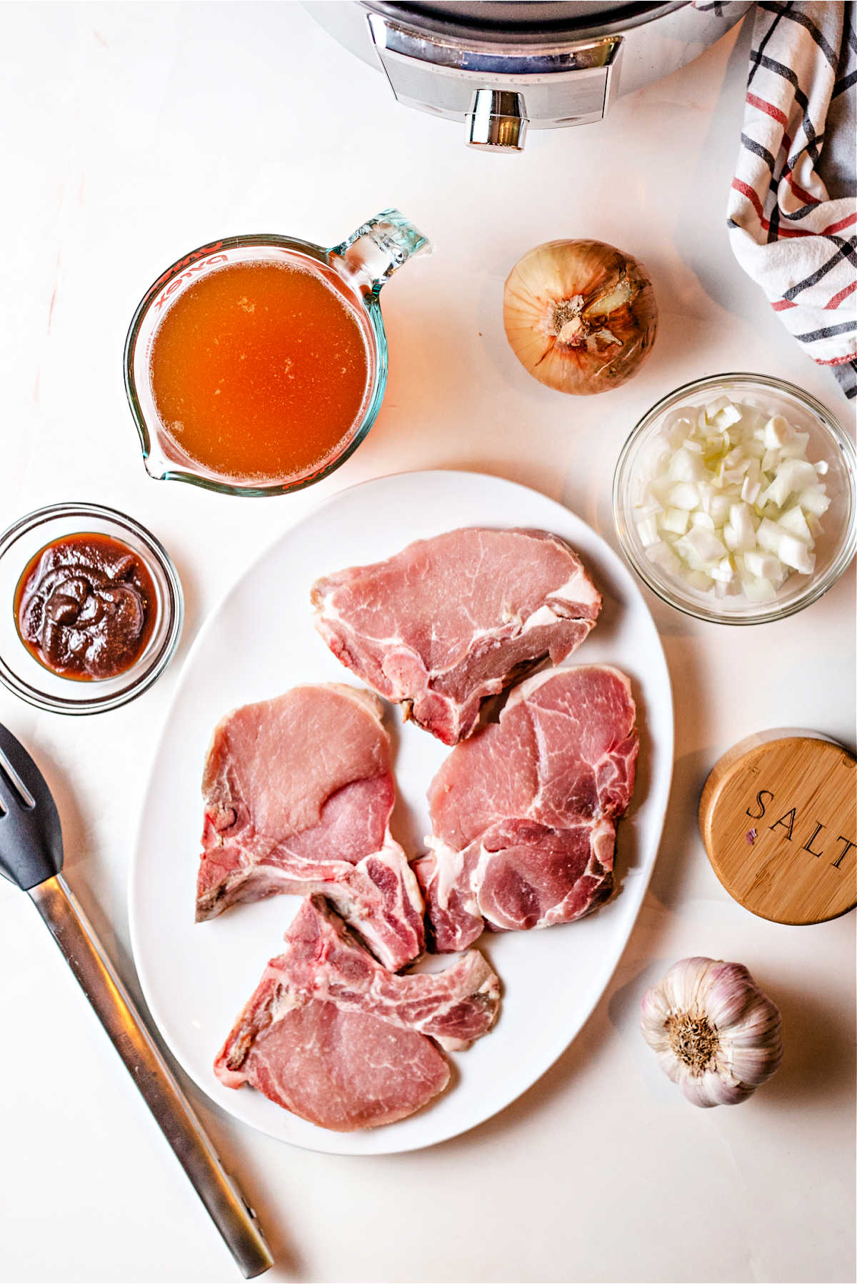 ingredients for instant pot pork chops on a counter: pork chops, apple butter, chicken broth, onion, and garlic.