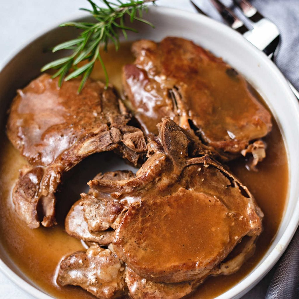 instant pot pork chops with gravy in a white serving dish.