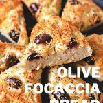 wedges of greek olive focaccia on a black stone platter.