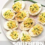 deviled eggs on a white plate garnished with paprika and freshly snipped chives.