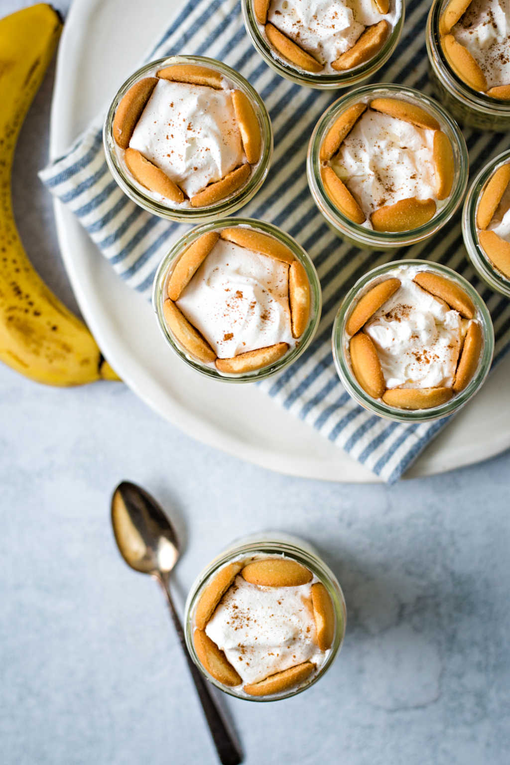 no bake banana pudding in small mason jars on white plate on a table.