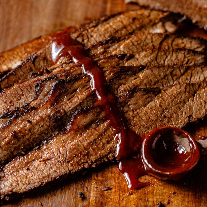 slices of beef brisket on a wooden board with BBQ sauce drizzled on top.