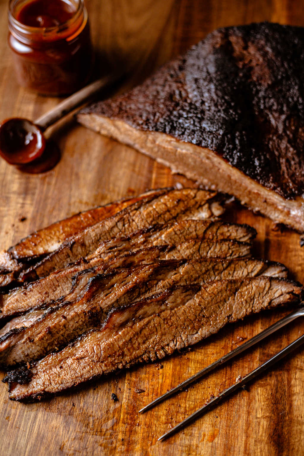 smoked beef brisket slices on a wooden board with a jar of bbq sauce.