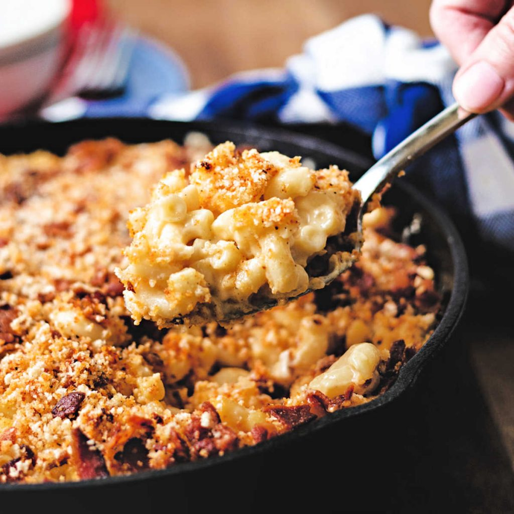 a spoonful of smoked mac and cheese being lifted out of a cast iron skillet.