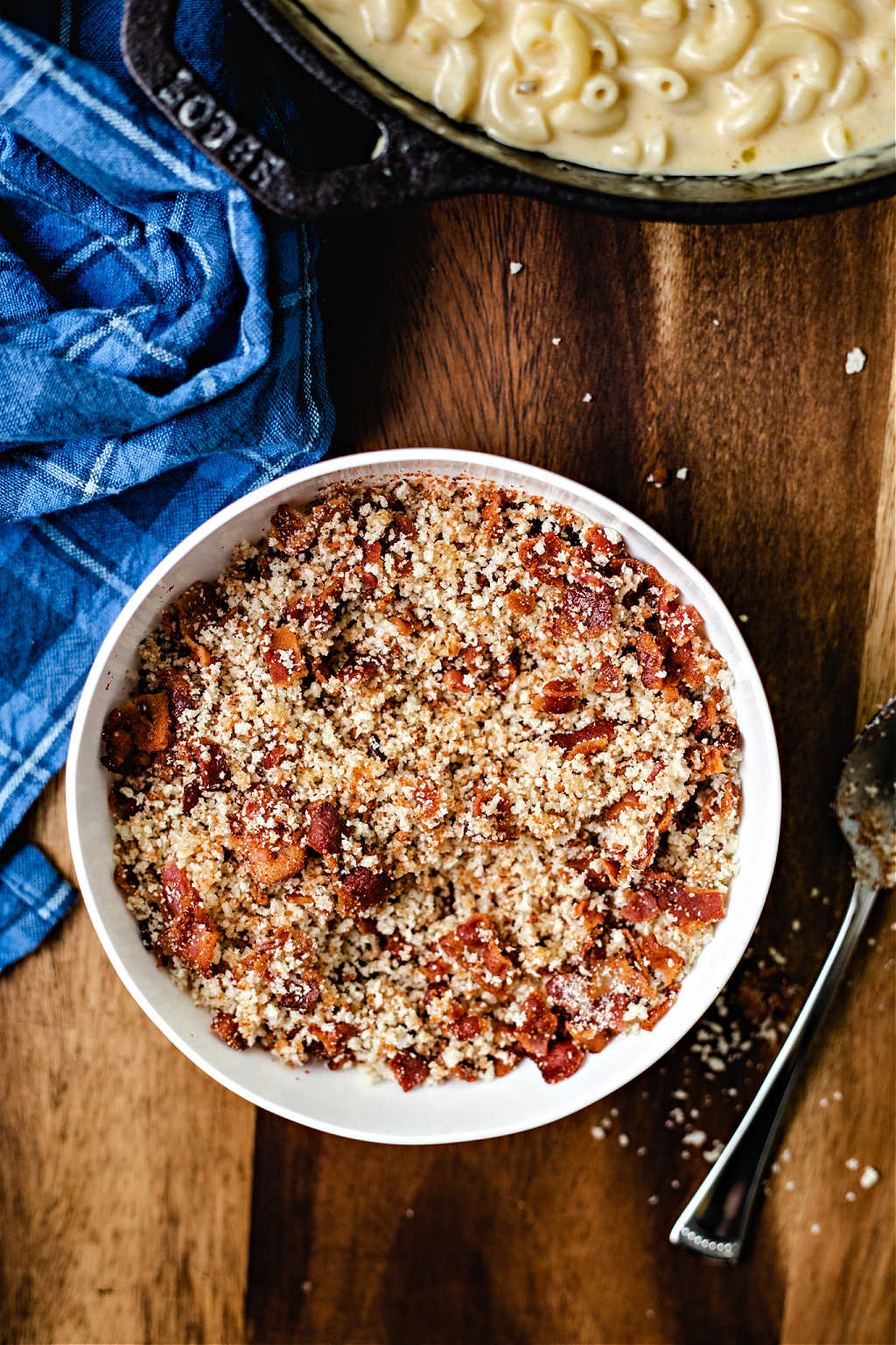 a bowl of bacon and panko crumb topping for smoked mac and cheese on a wooden table.