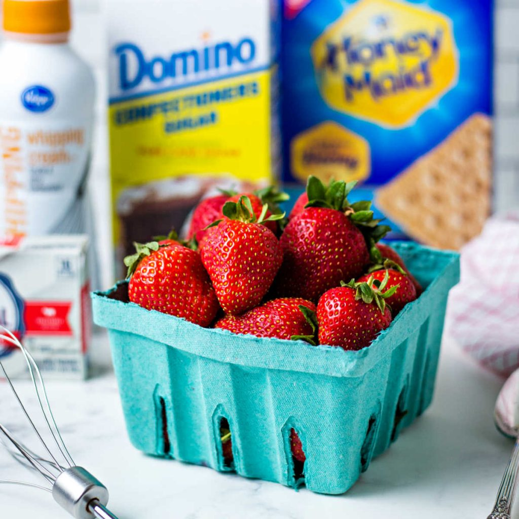 a box of strawberries on a kitchen counter with powdered sugar, graham crackers, and whipping cream in the background.