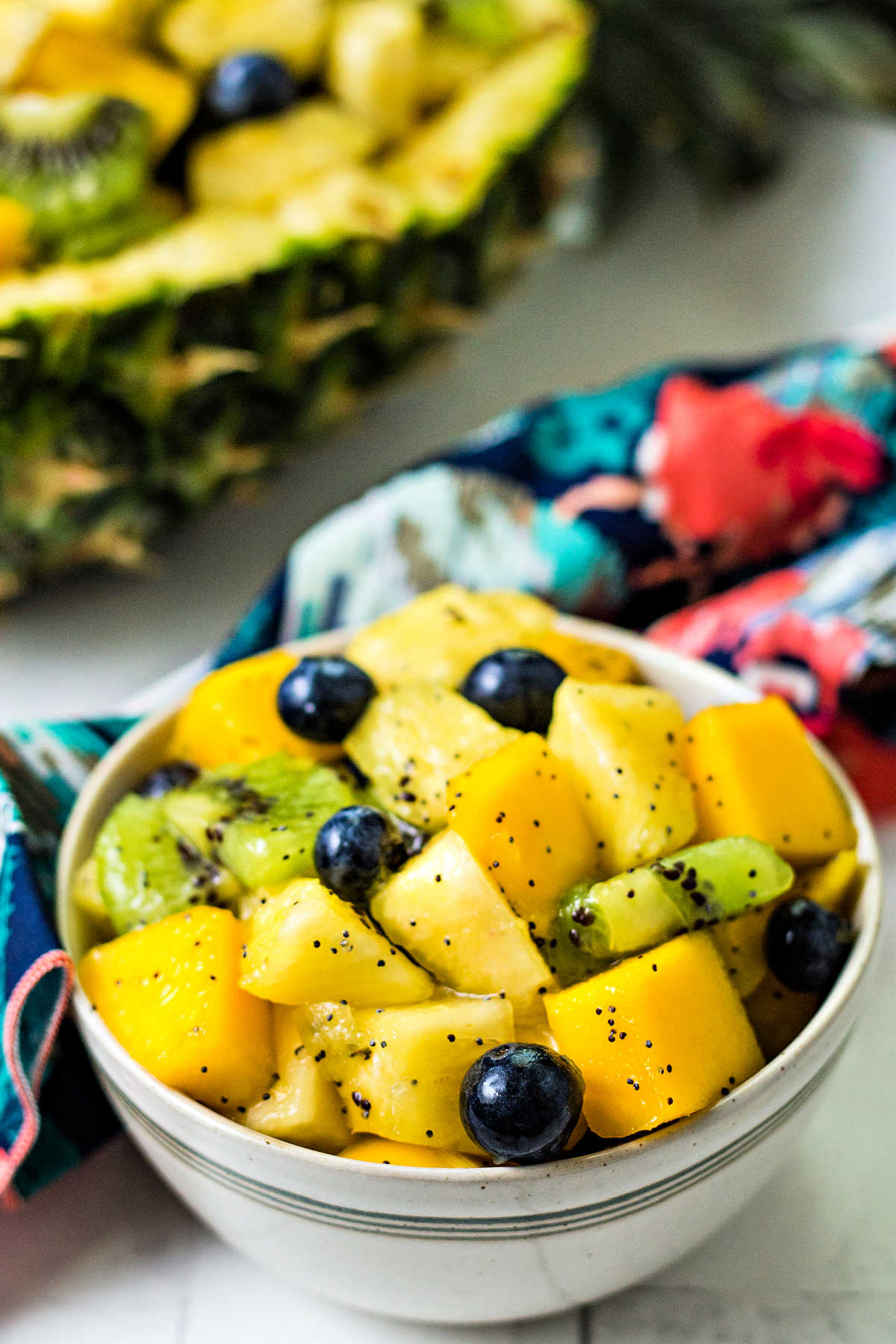 a bowl of tropical fruit salad on a table.
