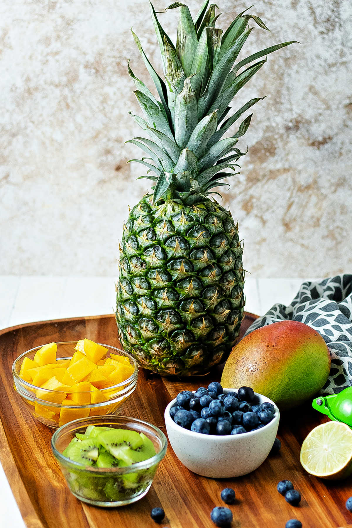 ingredients for tropical fruit salad on a wooden tray: fresh pineapple, mango chunks, sliced kiwi, and blueberries.
