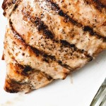 GRILLED CHICKEN BREAST ON A WHITE PLATE.