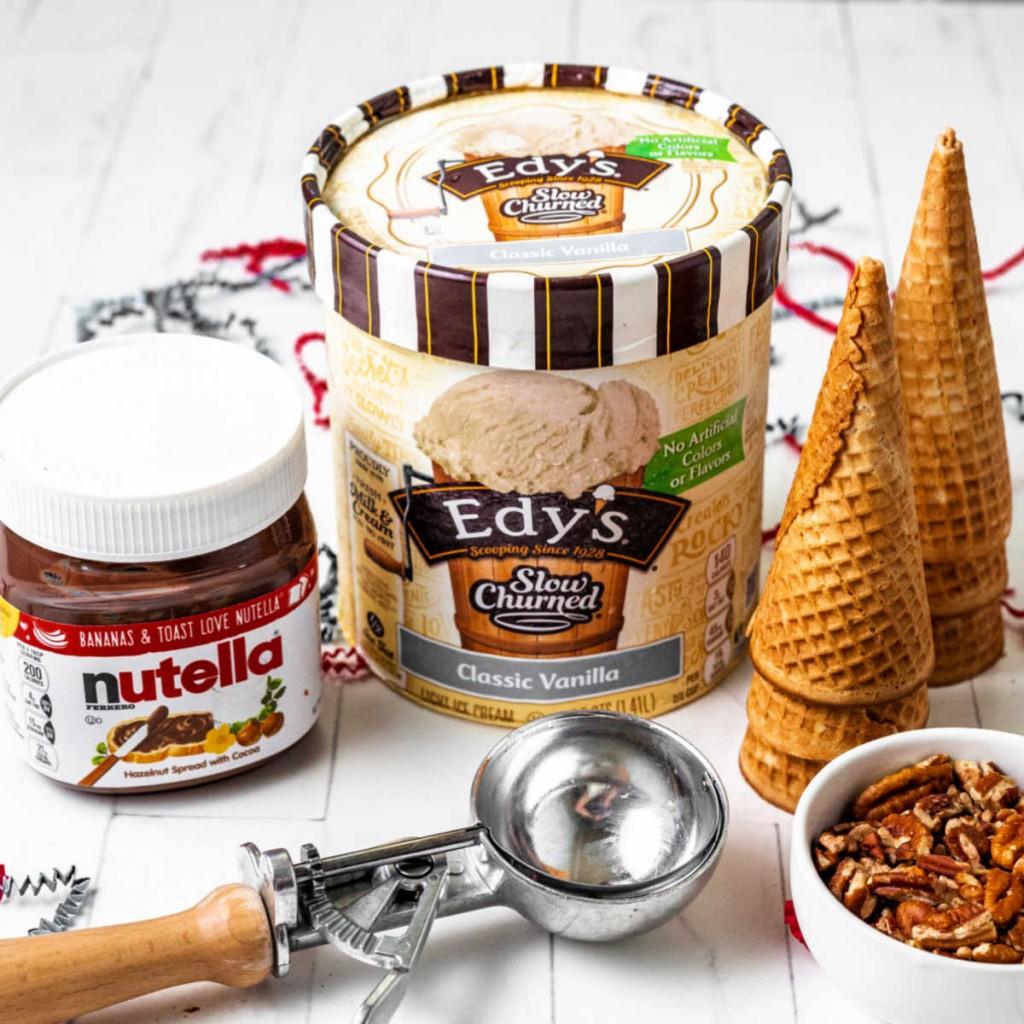 ingredients for an ice cream pie: nutella hazelnut spread, vanilla ice cream, sugar cones, and chopped pecans.