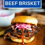 slices of beef brisket on a bun with red onions and barbecue sauce on a wooden table.