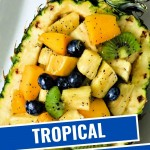 TROPICAL FRUIT SALAD IN A PINEAPPLE BOWL ON A WHITE PLATE.