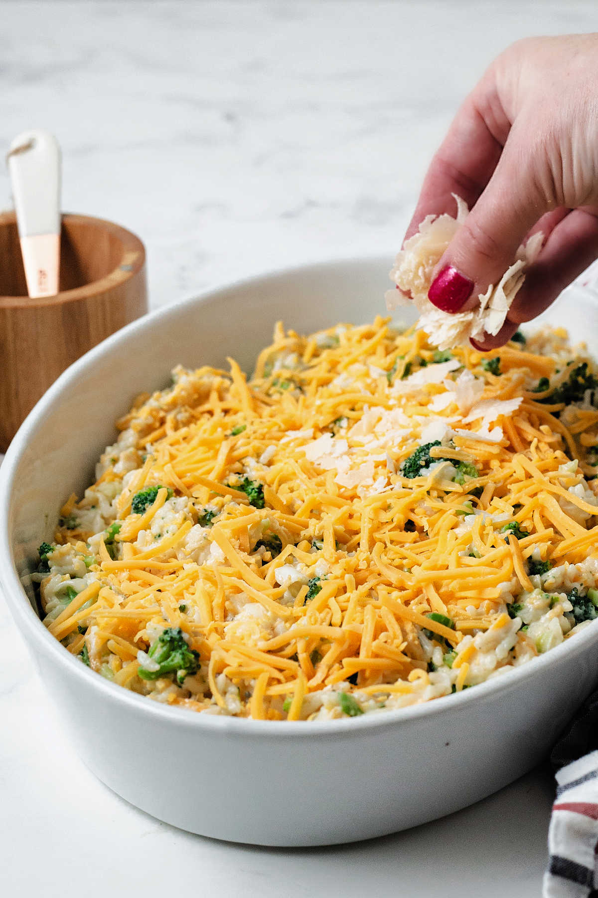 sprinkling shaved parmesan cheese on an unbaked casserole.
