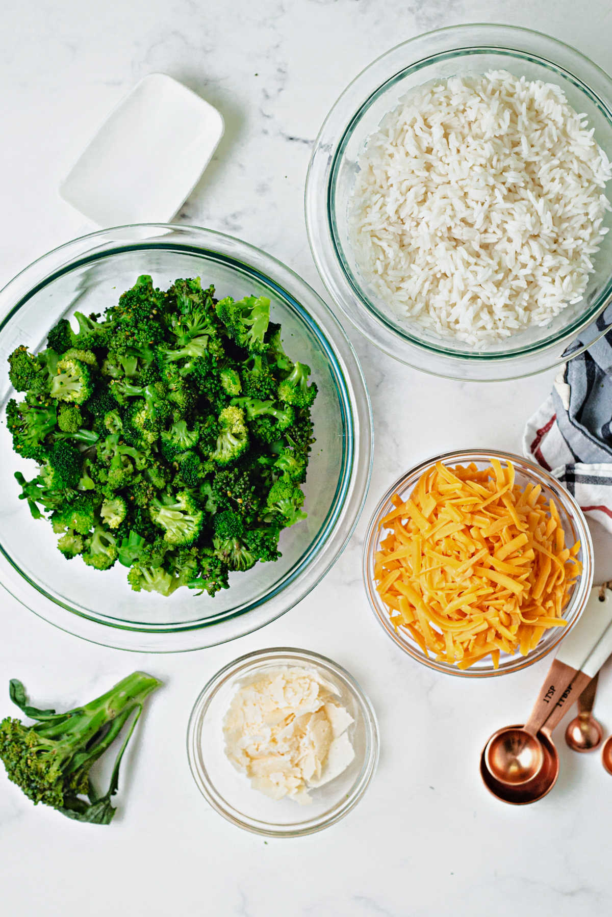 ingredients for a casserole: broccoli, rice, cheddar cheese, parmesan cheese.