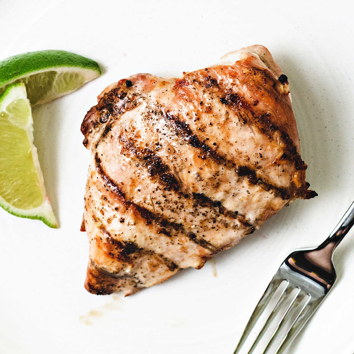 grilled chicken breast on a white plate with lime wedges and a fork.