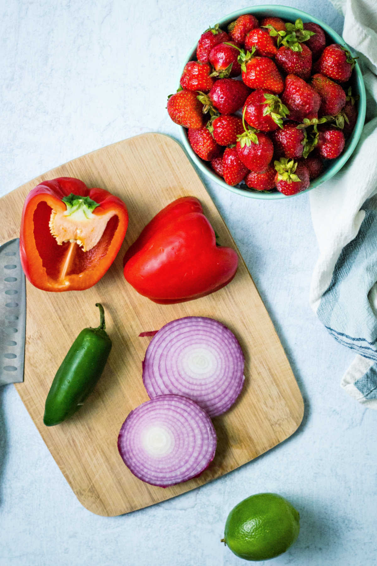 ingredients for strawberry salsa on a counter: a bowl of strawberries, red bell pepper, jalapeno, red onion slices, and a lime.