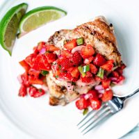 a grilled chicken breast with strawberry salsa spooned over top on a white plate.