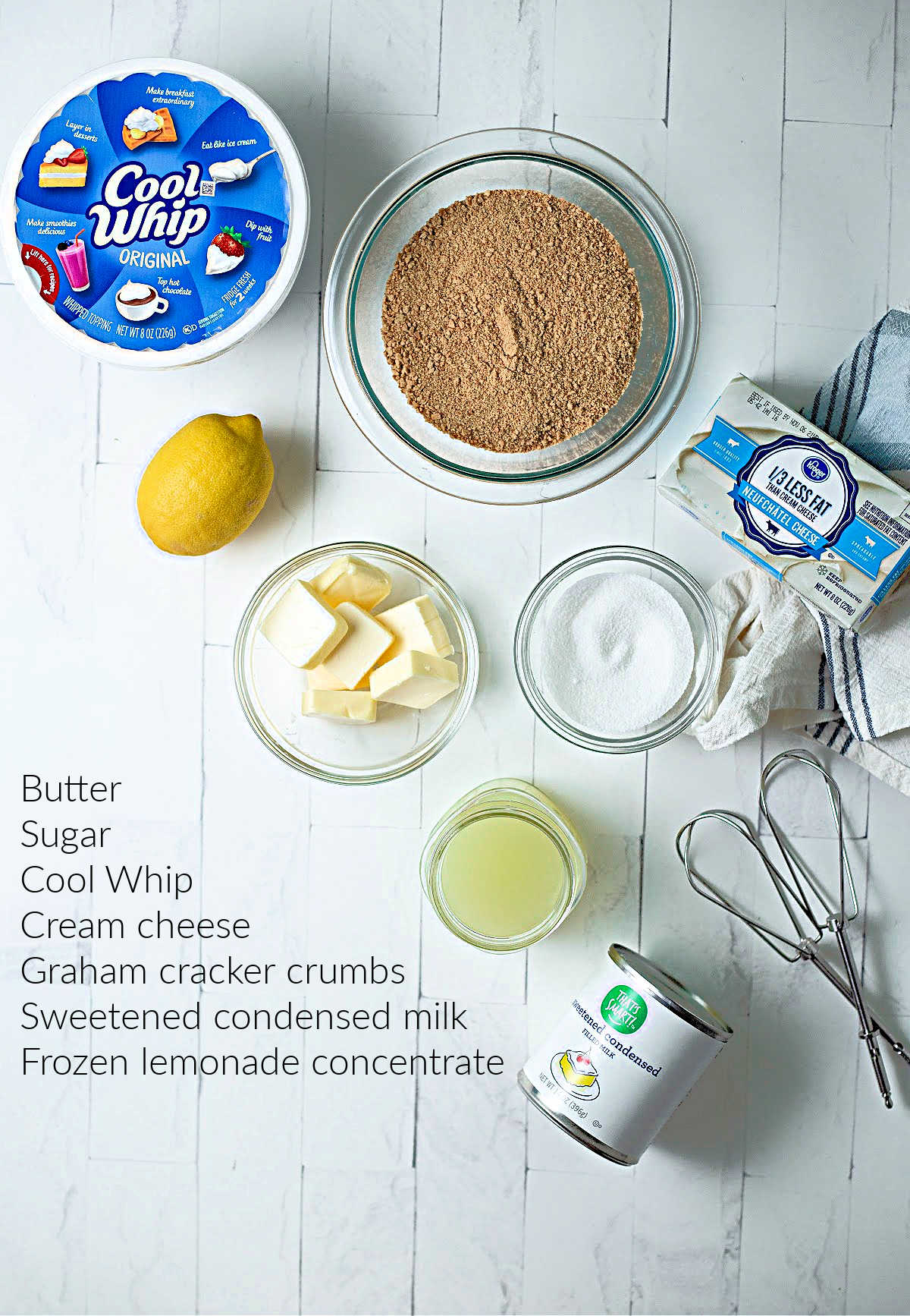 ingredients for lemonade pie on a table: Cool Whip, crushed graham crackers, butter, sugar, lemonade, sweetened condensed milk, and cream cheese.