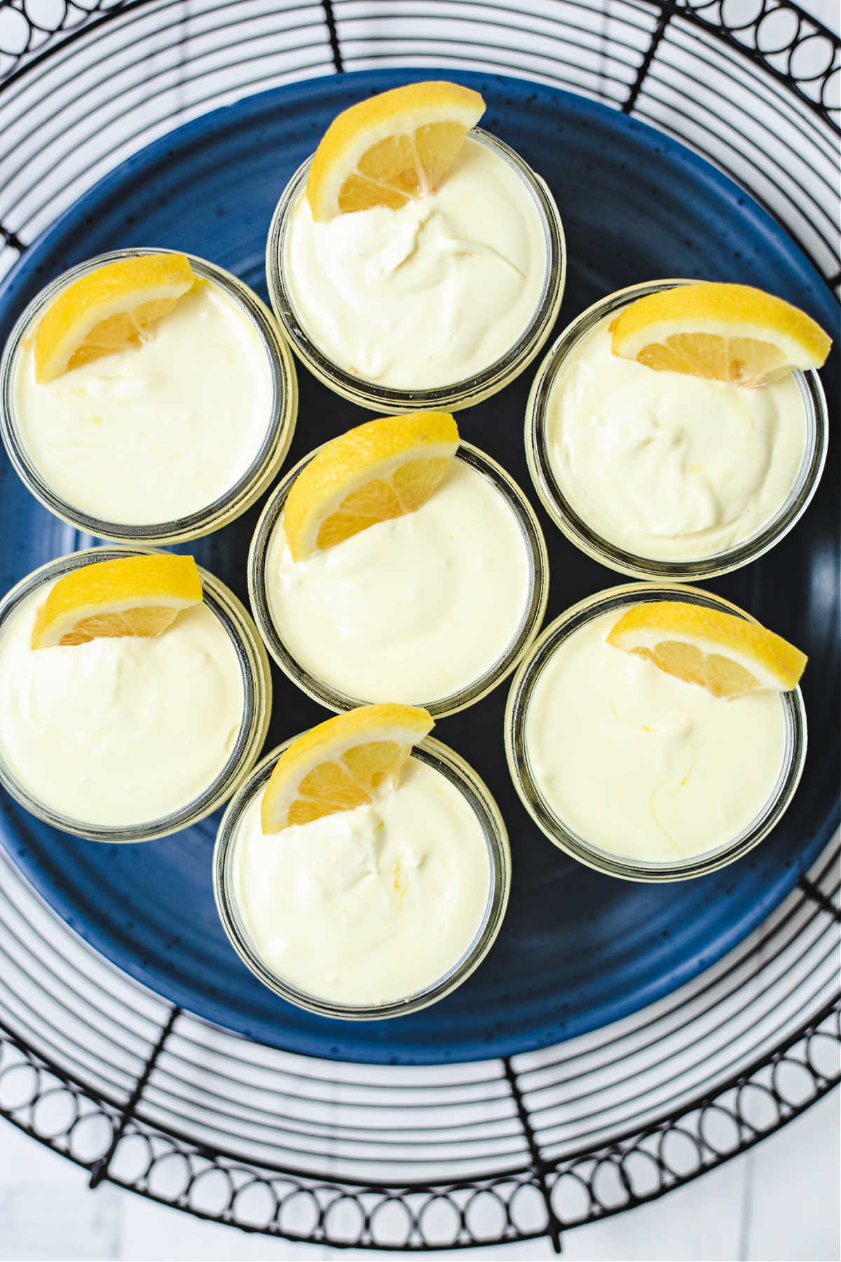 top down view of lemonade pies in small mason jars on a slate plate.