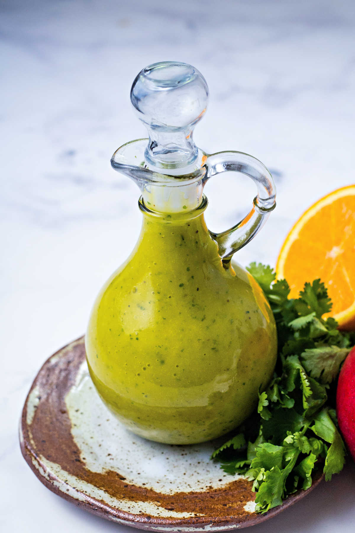 a decorative carafe filled with mango dressing sitting on a table surrounded by cilantro, an orange slice, and a mango.