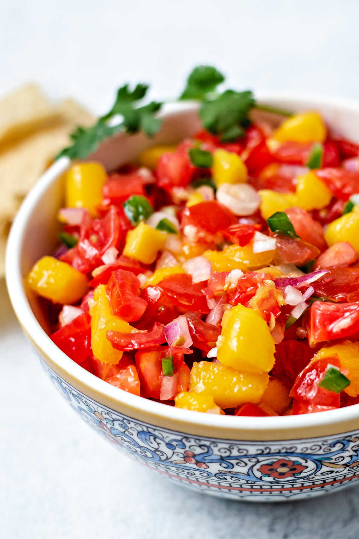 close up image of mango tomato salsa in a bowl on a table.