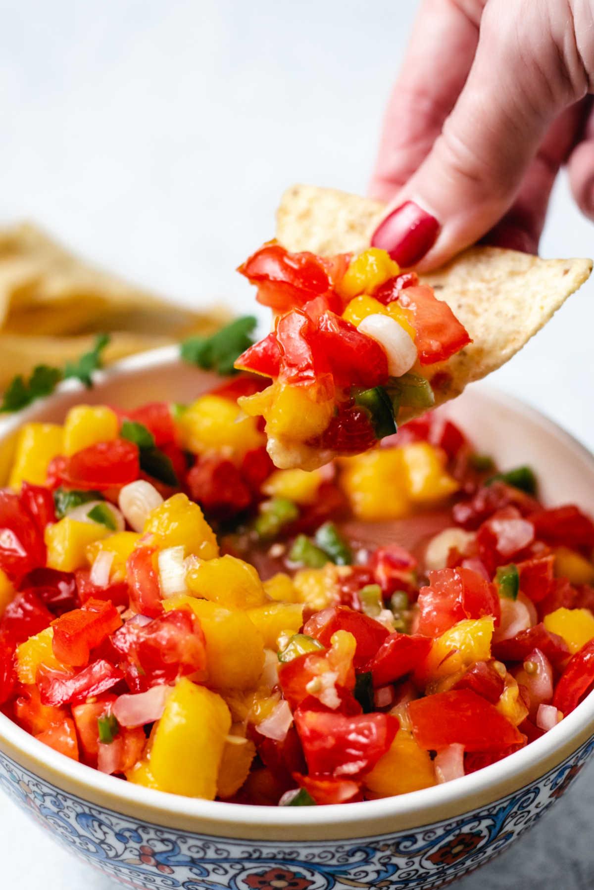 dipping a tortilla chip into a bowl of mango tomato salsa.