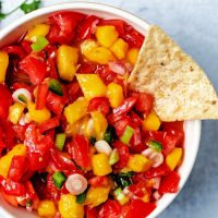 mango tomato salsa in a bowl with a tortilla chip dipping into the bowl.