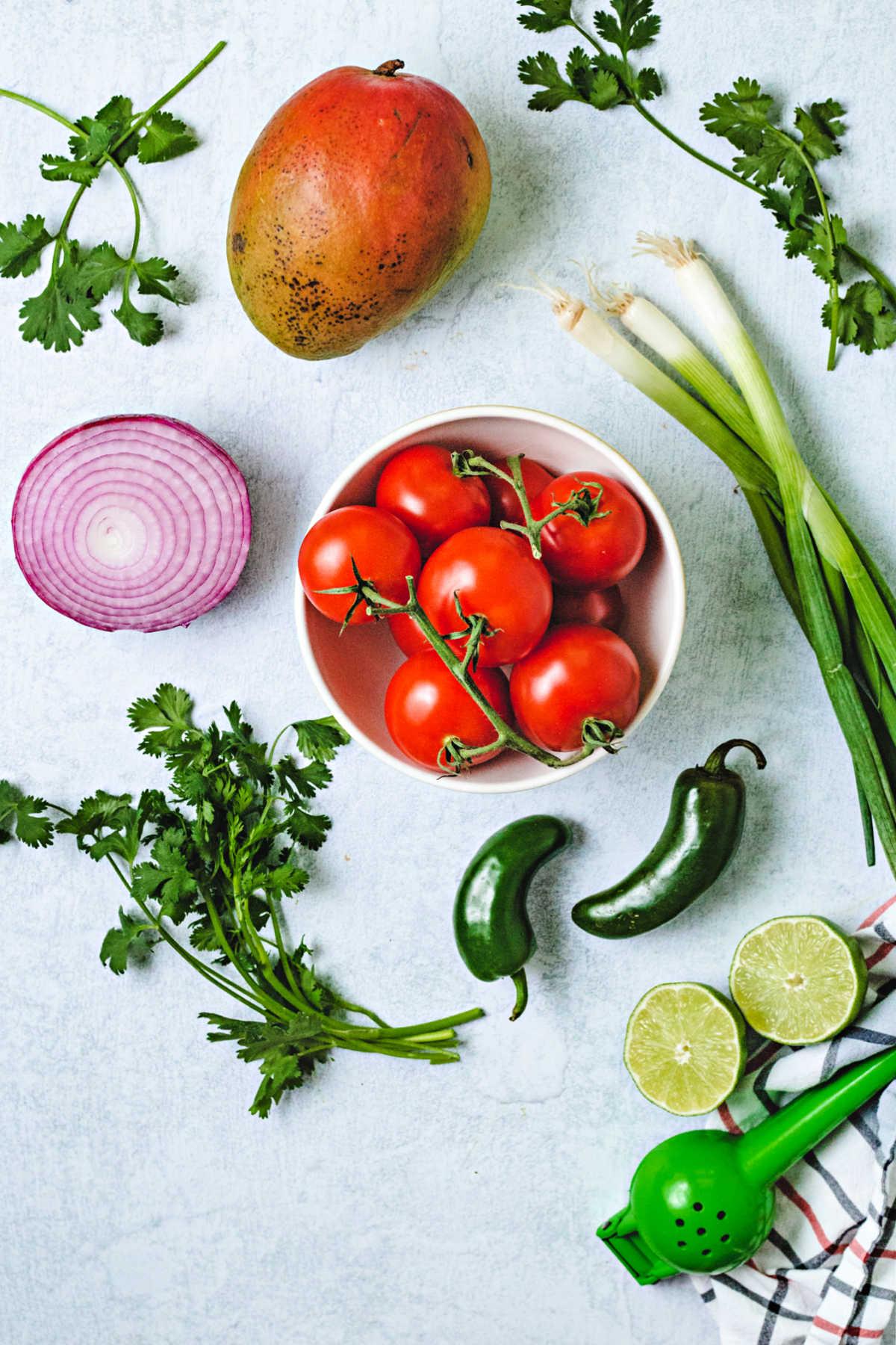 ingredients for mango salsa: tomatoes, mango, cilantro, red onion, scallions, lime, and jalapeno.