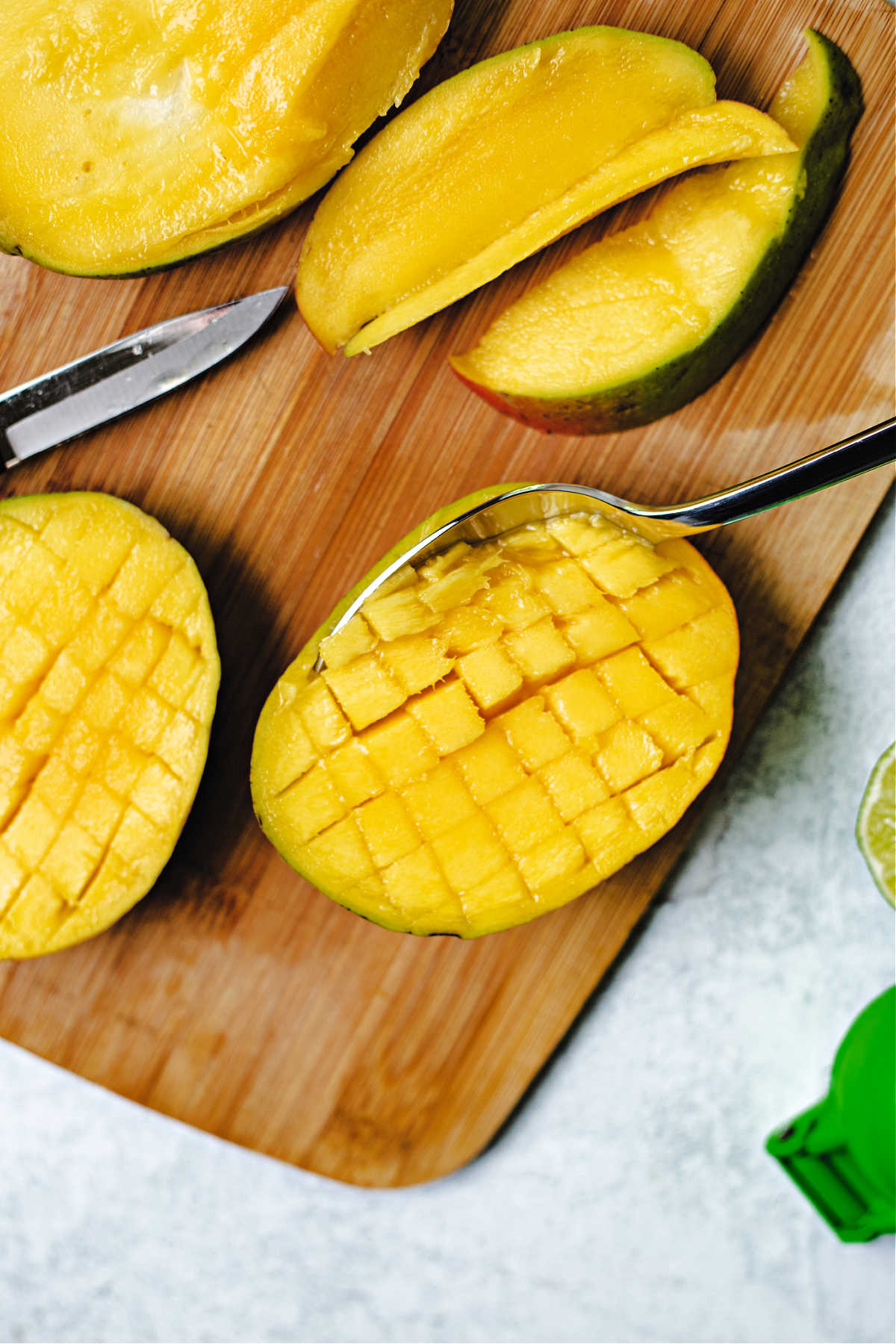 scooping mango out of the peel.