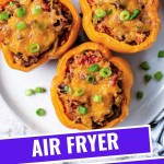 air fryer stuffed peppers with melted cheese on a plate garnished with chopped green onions.