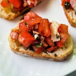 a slice of bruschetta with tomato salad on a white plate.