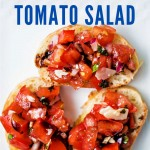 3 slices of bruschetta with tomato salad on a white plate.