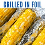 an ear of grilled corn with holders in each end on a crumpled piece of aluminum foil on a blue plate.