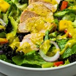 close up image of a chopped salad with slices of grilled chicken dressed with mango dressing.