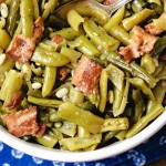 a bowl of green beans sitting on a blue napkin on a wooden table.