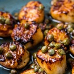 seared scallops with brown butter sauce on a blue plate with capers.