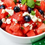 cubes of watermelon, blueberries, crumbled feta cheese, and fresh mint in a white bowl on a table.