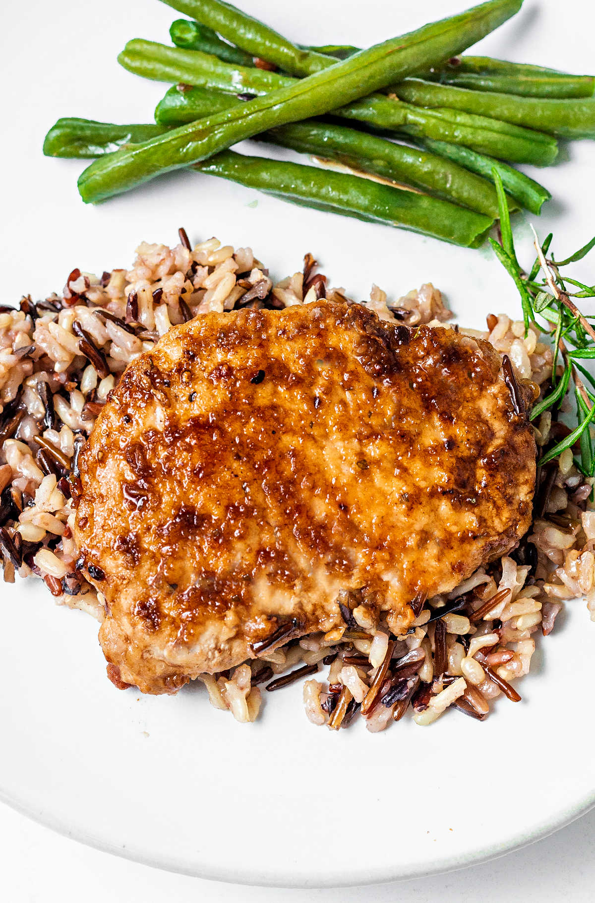 pork chop on a bed of rice on a plate with green beans and a sprig of rosemary on a table.