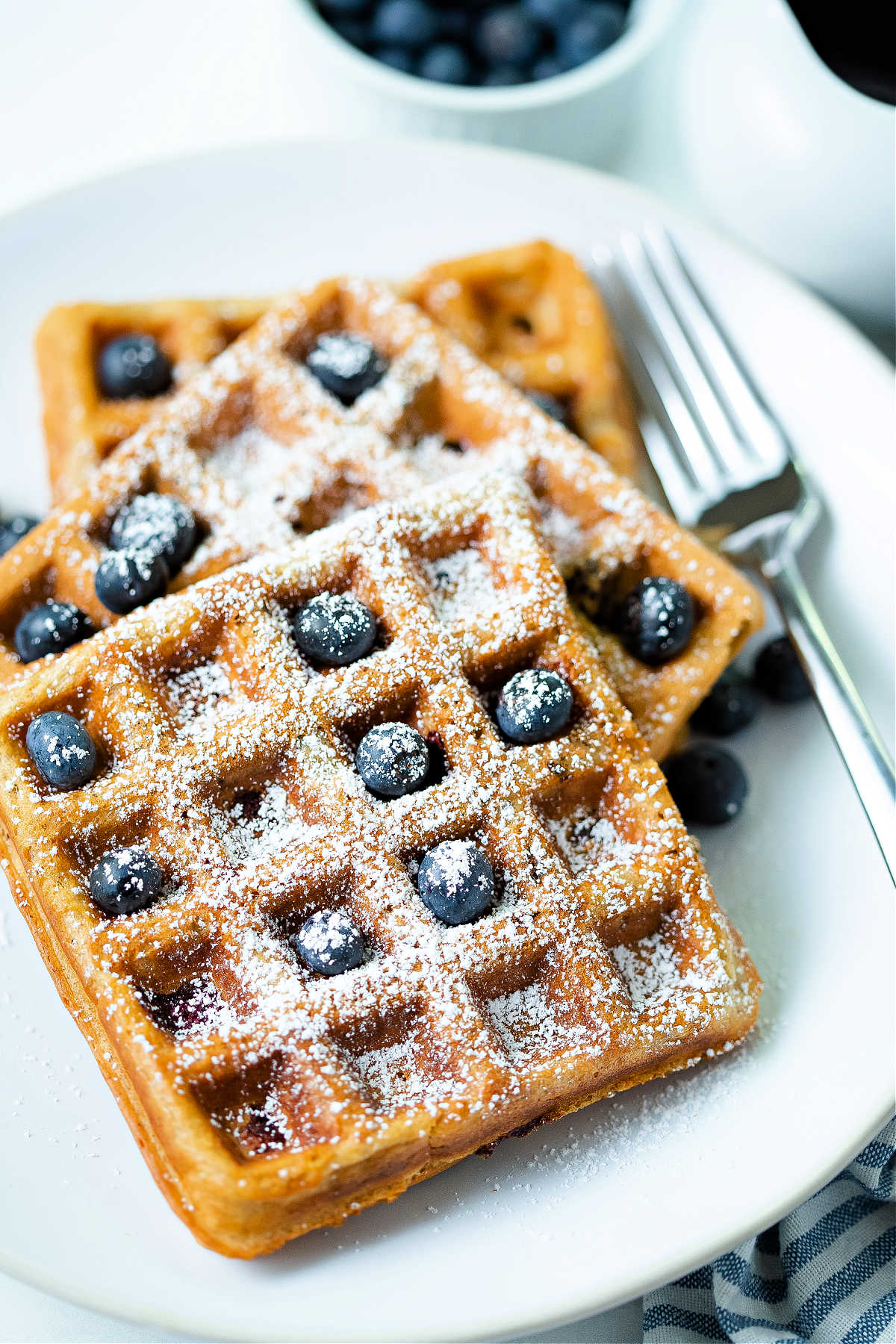 three blueberry waffles on a white plate with a fork to the side.
