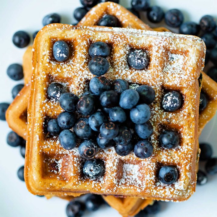 top down view of blueberry waffles stacked on top of each other with fresh blueberries scattered around on a white plate.
