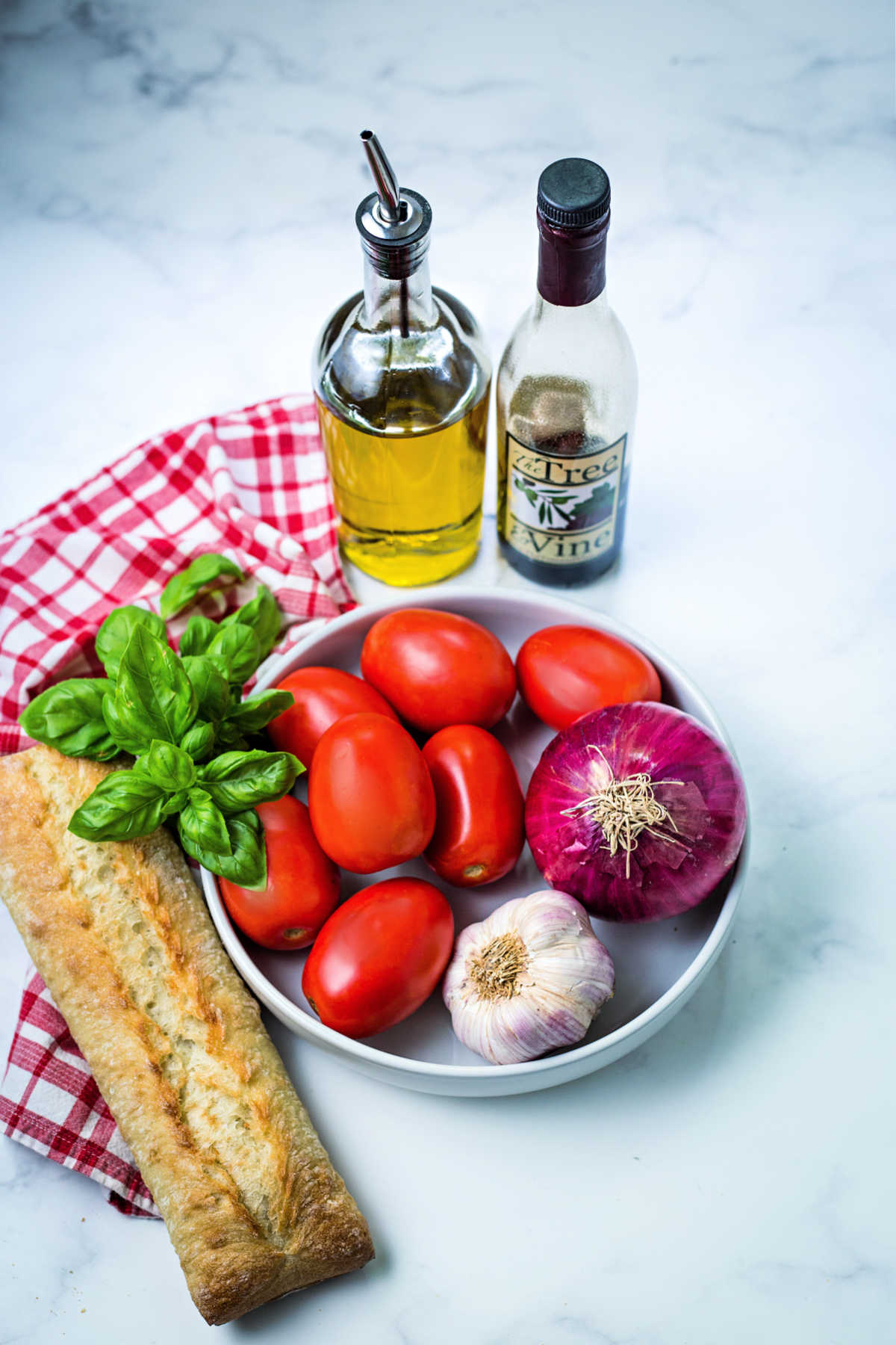 ingredients for bruschetta on a kitchen counter: roma tomatoes, basil, garlic, red onion, olive oil, and balsamic vinegar.