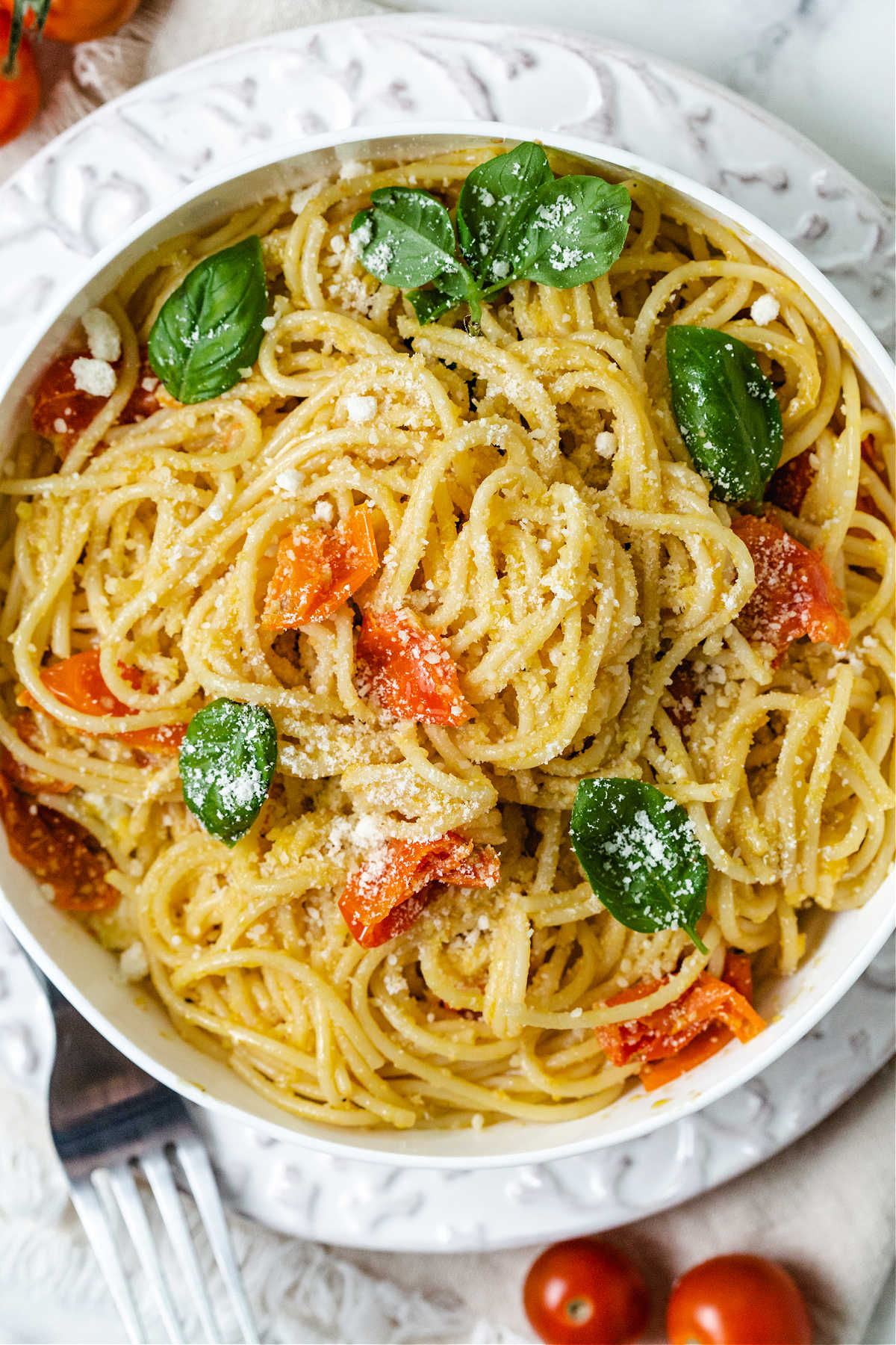 a bowl of pasta with roasted cherry tomato pasta sauce and fresh basil leaves.