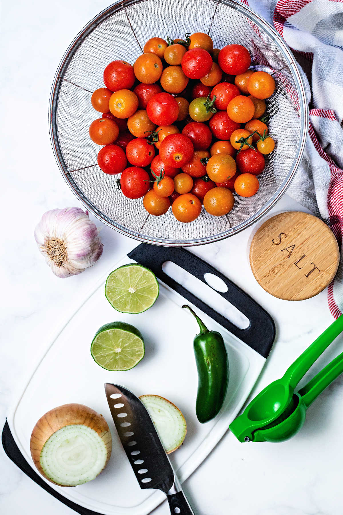 ingredients for cherry tomato salsa on a counter: cherry tomatoes in a mesh colander, garlic, white onion, jalapeno, lime, and a salt box.