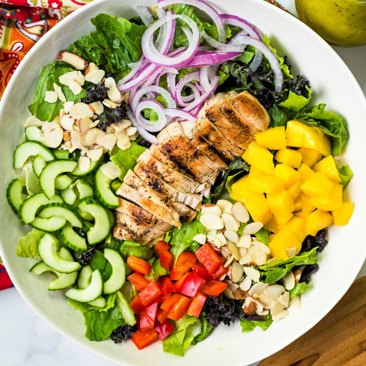 a large salad bowl with salad greens, chopped mango, cucumber, red bell pepper, red onions, and almonds with a sliced grilled chicken breast laying on top.