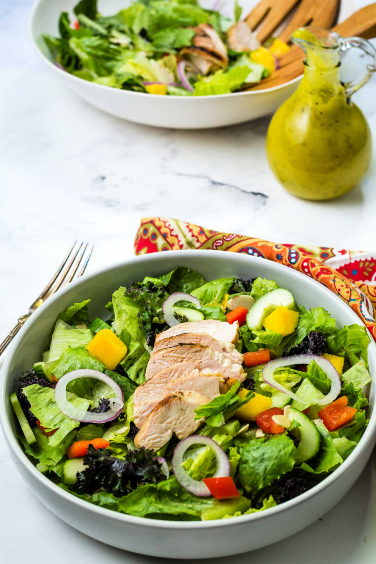 grilled chicken salad in a bowl on a table with a bottle of mango dressing.
