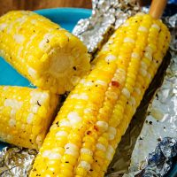 an ear of corn grilled in foil on a plate.