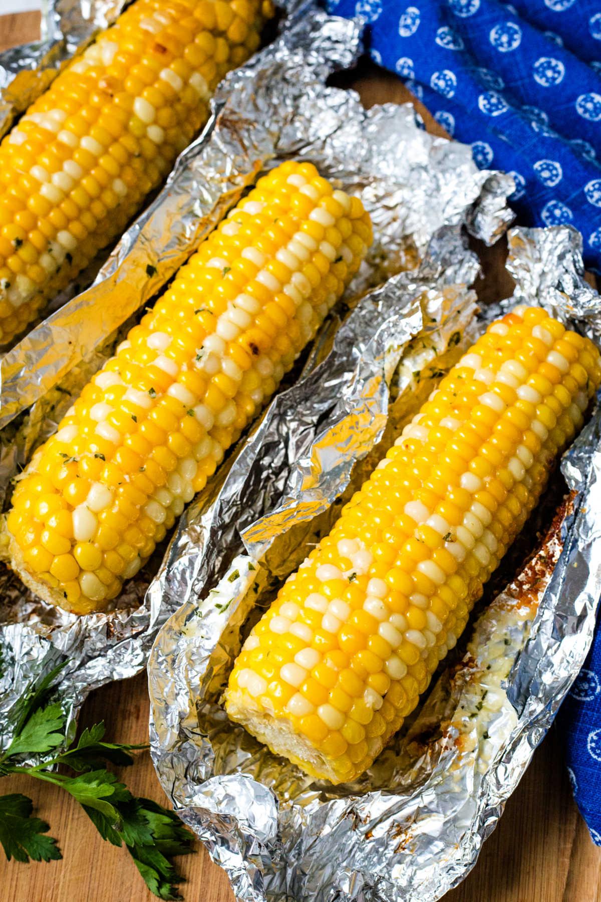 3 unwrapped ears of grill corn in foil on a wooden board.